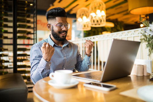 Overjoyed hipster indian guy cheers for team watching match on laptop computer during free time in cafe interior, amazed emotional male freelancer celebrating achievement and completing project