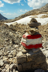 Carstic landscape with a pile of stones stacking up and touristic mark on background, Austria