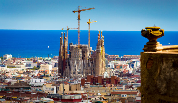 Sagrada Familia with sea in background and bit of wall in foreground