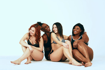 Multiethnic diverse women with cheerful expression smiling and hugging together, sit in group on the floor, dressed in underwear, isolated over white background. Interracial lesbian couple.