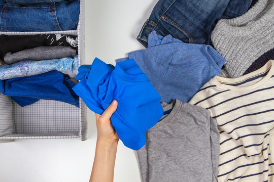 Vertical storage of clothing, tidying up, room cleaning concept. Hands tidying up and sorting kids clothes in basket.