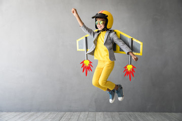 Happy child playing with toy jetpack