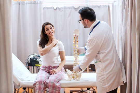 Female patient in pajamas sitting on hospital bed and showing hurting place on neck. Doctor standing next to her and holding spine model.