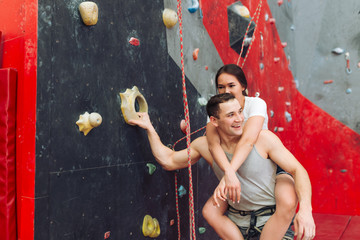 trainer typing harness of woman on climbing wall in gym. close up photo. happiness concept