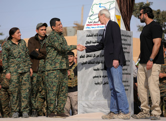 Mazloum Kobani, SDF's commander in chief, shakes hands with advisor for the US Department of State in northern Syria William Robak, at al-Omar oil field in Deir Al Zor