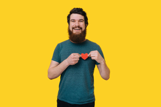 Handsome happy bearded man looking at the camera, holding a red heart upon his chest on yellow background.