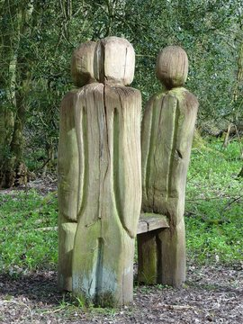 Standing wooden carved characters surrounding bench, Philipshill Wood, Chorleywood