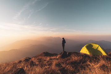 Foto auf Leinwand Dunkelbraun Young man traveler looking landscape at sunset and camping on mountain, Adventure travel lifestyle concept