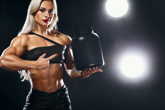 Athletic young woman bodybuilder on steroids have a cheat meal. Fitness and sport concept. Nutrition and bodybuilding.