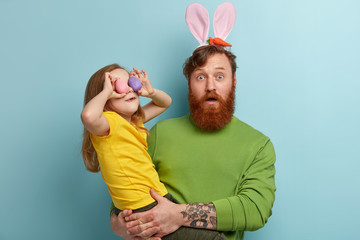 Scared emotional red haired man with bunny ears carries little cheerful girl who holds two colored eggs on eyes, celebrate Easter together, isolated over blue wall. Dad with kid prepare for holiday