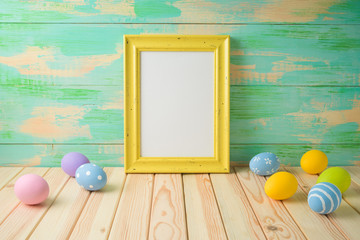 Photo frame or artwork display mock up on wooden table with easter eggs.