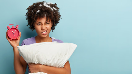 Irritated black woman wants to kill ringing alarm clock, frowns face and clenches teeth, holds soft white pillow, feathers on hair, being just after sleep, stands over blue studio wall. Free space
