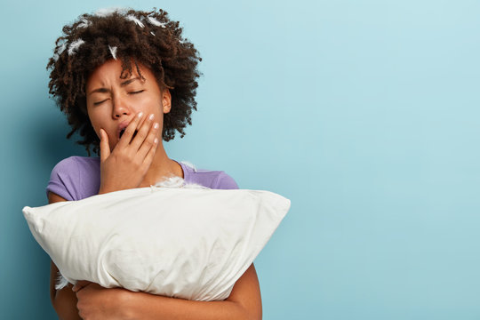 Sleepy tired young Afro American woman covers mouth with hand, yawns after sleep, embraces white pillow, has feathers in head, poses over blue background with blank space for your promotion.