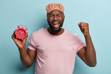 Isolated shot of annoyed black man raises fist and shouts loudly from despair, irritated with sound of alarm clock, dressed in sleepwear, poses alone. Crying sad African American male with clock