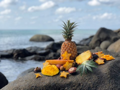 juicy fresh Thai fruit mango, pineapple, mangosteen, papaya on a stone against the sea and cloudy blue sky in the afternoon