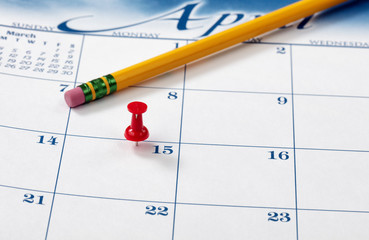 Single red pushpin on April 15 of calendar for tax income due date reminder on desktop with pencil
