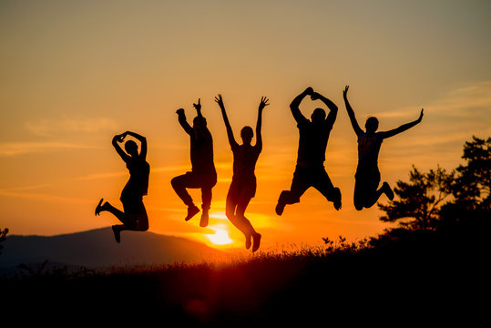 group of cheerful friends are jumping together at amazing sunset in the background of the mountains