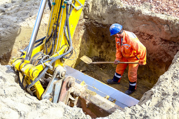 Worker is using shovel to set up right measures in square trench