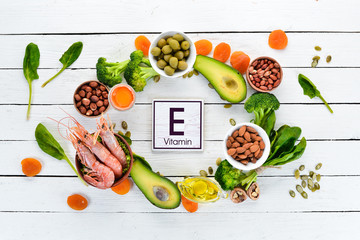 Food containing natural vitamin E: Spinach, parsley, shrimp, pumpkin seeds, eggs, avocados, broccoli. Top view. On a white wooden background.