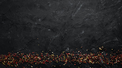Wall Mural - Peppers and spices on a black background. Top view. Free space for your text. Rustic style.