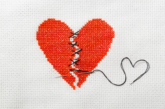 The broken red heart is threaded with black threads. Heart embroidered on white cloth.
