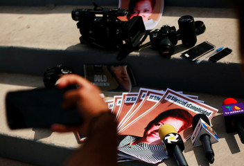 Microphones and cameras, left by members of the media, are seen next to the pictures of their colleague Miroslava Breach during a protest to mark the second anniversary of her murder, outside the state government offices in Ciudad Juarez