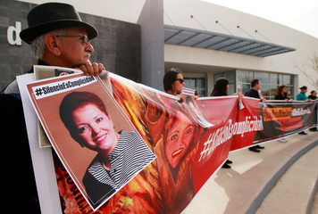 Members of the media hold up a banner and signs with pictures of their colleague Miroslava Breach during a protest to mark the second anniversary of her murder, outside the state government offices in Ciudad Juarez