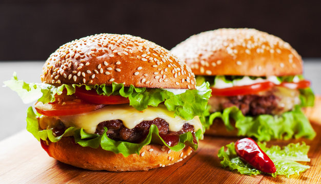 two burger with meat, cheese and vegetables on wooden board
