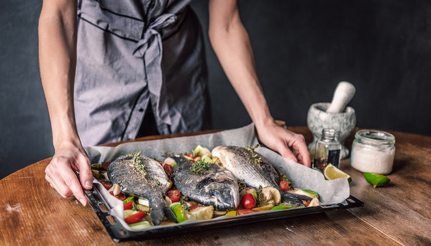 mother cooks dinner for the whole family, bakes dorado fish