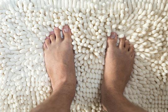 Male legs on fluffy carpet