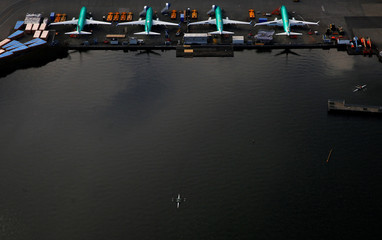 An aerial photo shows rowers on Lake Washington near a line of Boeing 737 MAX aircraft at the Boeing factory in Renton