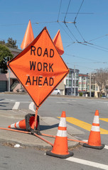 Orange ROAD WORK AHEAD sign with safety cones and flags.