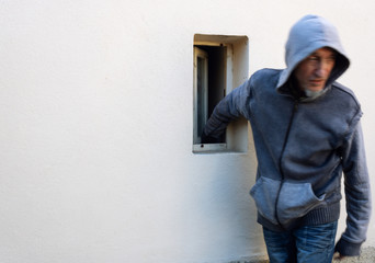 Burglar or thief or robber with face motion blur is stealing with arm through the small window