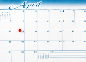 Single red pushpin on April 15 of calendar for tax income due date reminder in overhead view