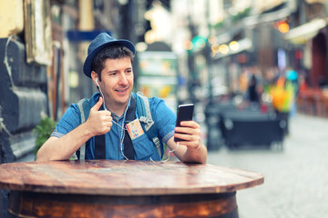 Traveler with trendy look having a video call showing thumb up while enjoy exploring streets of big cities - Man vlogging in old town – tourist sharing experience with friends on social media