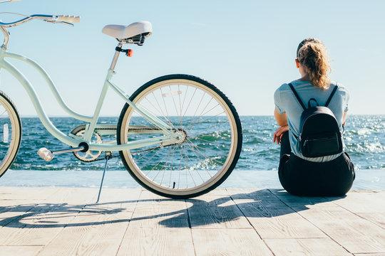Female wearing backpack resting after bike ride