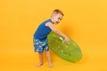 Kid boy 3-4 years old in blue beach summer clothes hold inflatable ring isolated on bright yellow orange wall background children studio portrait. People childhood lifestyle concept Mock up copy space