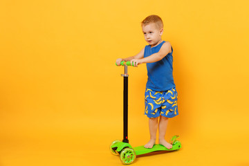 Wall Mural - Kid boy 3-4 years old wearing blue beach summer clothes on scooter isolated on bright yellow orange wall background, children studio portrait. People, childhood lifestyle concept. Mock up copy space.
