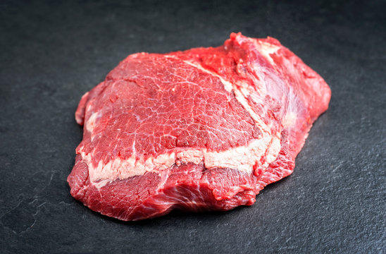 Traditional raw beef cheeks as closeup on a black board
