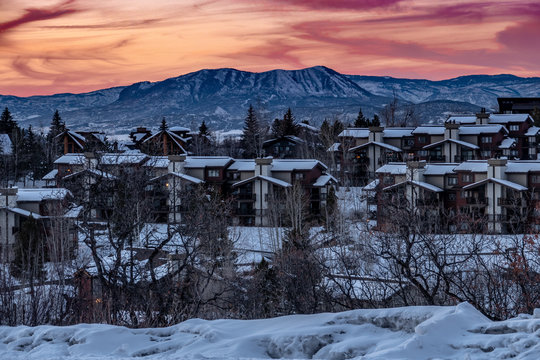 Snow covered condominiums at sunset, near the ski slopes of the Steamboat Springs Resort, in the Rocky Mountains of Colorado.  A mountain peak known as the Sleeping Giant, is seen in the background.