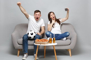 Fun couple woman man football fans cheer up support favorite team, expressive gesticulating hands, showing thumb up doing selfie shot on mobile phone isolated on grey background. Sport family concept.