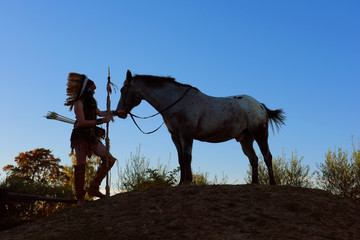 A young girl plays the part of a native American Indian  girl. She poses on top of a small hill with her horse. The photo reveals the feeling of the sun going down.