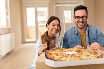 Happy couple eating pizza.