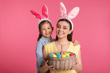 Mother and daughter in bunny ears headbands with Easter eggs on color background