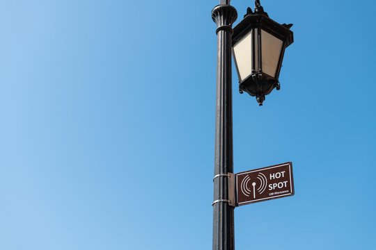 Warsaw, Poland Famous old town capital city during sunny summer day background blue sky and closeup of sign for Warszawa Wifi Hot Spot on lantern lamp pole
