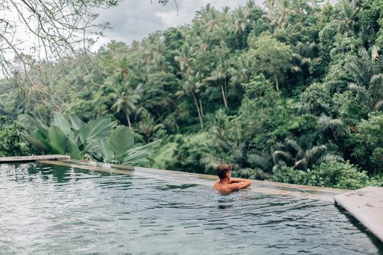 Human swimming in Bali infinity pool