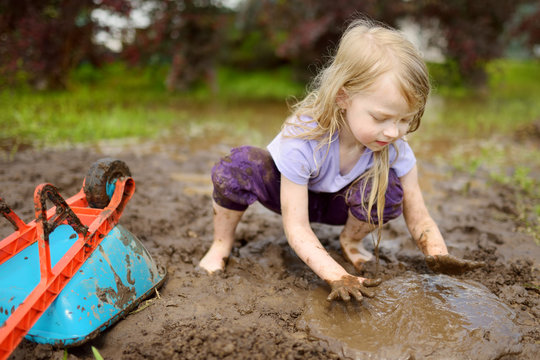 Funny little girl playing in a large wet mud puddle on sunny summer day. Child getting dirty while digging in muddy soil.