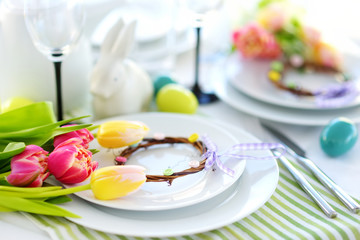 Beautiful table setting with crockery and flowers for Easter celebration.