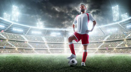 Soccer professional player preparing to the match. Foot on the soccer ball. Night Stadium background. Sport concept