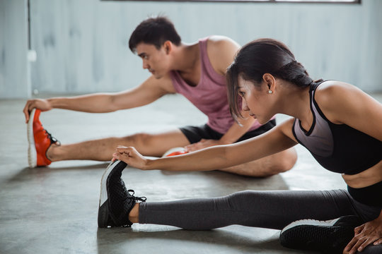 a couple doing stretching together at the fitness centre
